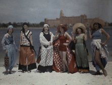 Women pose, in their beach attire, on a white sand beach in Florida.