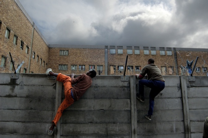 A sentenced prisoner and an awaiting-trial prisoner climb over a dividing wall at Pollsmoor Maximum Security Prison. Sentenced and awaiting-trial prisoners are supposed to be completely separated, but a combination of overcrowding and understaffing means that there is very little control over movement within the prison.